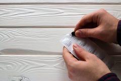 Mann öffnet ein Paket der Aktivkohle Stockbild