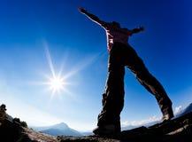 Mann öffnet seine Arme im Sonnenschein gegen blauen Himmel. Stockbilder
