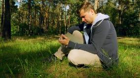 Mann öffnet und liest Buch im Park und sitzt auf dem Gras stock footage