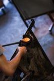 Mann übergibt die Nahaufnahme, die an einem geblasenen Glasstück arbeitet Stockfotos