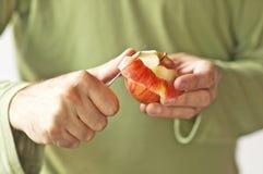 Mann übergibt die Schale eines Apfels Stockfotografie