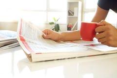 Mann übergibt Lesezeitung stockbilder
