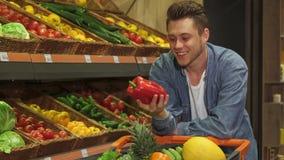 Mann überprüft grünen Pfeffer am Supermarkt stock video