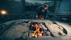 Mann überprüft Kohle auf Feuer an einer Schmiede stock video