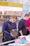 Mann überprüft und wählt Bücher vor Stockbilder