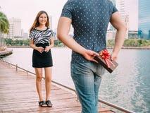 Mann überrascht seine Freundin, indem er heraus ein Geschenk - Liebes- und Verhältnis-Konzept gibt Lizenzfreie Stockbilder