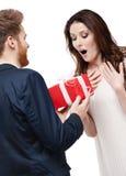 Mann überrascht seine Freundin mit Geschenk Stockbilder