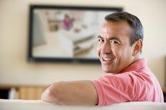 Mann in überwachendem Fernsehen des Wohnzimmers Lizenzfreie Stockfotografie