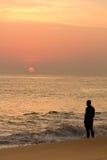 Mann überwacht rote Sonne am Sonnenuntergang Stockbilder