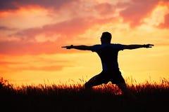 Mann übt Yoga während des Sonnenuntergangs Stockfoto