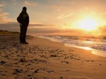 Mann in Abendmeer Tourist in der dunklen Kleidung und im Rucksack entlang Strand Stockbild