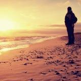 Mann in Abendmeer Tourist in der dunklen Kleidung und im Rucksack entlang Strand Lizenzfreies Stockfoto