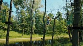 Mann Abenteuer-im hohen Seil-Park, der kletternde ?bungen im Sommer tut stock video