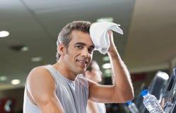 Mann-Abwischen geschwitzt mit Tuch am Fitnessstudio Stockfotografie