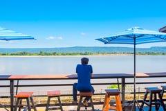 Mann allein sitzen auf dem allein nahen Flussufer des Balkons Lizenzfreies Stockbild