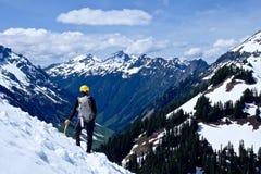 Mann-Alpinist, der auf die Gebirgsoberseite steht Stockfotografie