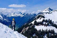Mann-Alpinist, der auf die Gebirgsoberseite steht Lizenzfreie Stockbilder