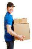 Mann als Lieferungskerl, der Pakete hält Stockfotografie