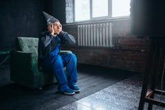 Mann in Alufoliekappen-Uhr Fernsehen, Telepathiephobie Stockbild