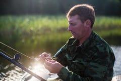 Mann in Angelrute der Tarnung auf dem Fluss auf einem Gummiboot liebhaberei lizenzfreies stockfoto
