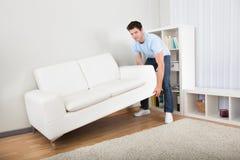 Mann-anhebende Couch Lizenzfreie Stockfotos