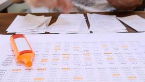 Mann-Arbeiten mit den Rechnungen, die jährliches Familien-Budget zählen stock video