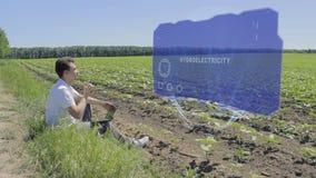 Mann arbeitet an ganz eigenhändig geschrieber Anzeige HUDs mit Text Hydroelektrizität am Rand des Feldes stock video footage