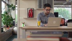 Mann arbeitet im Coworking mit Laptop stock footage