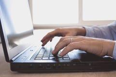 Mann arbeitet an Laptop Stockfoto