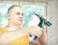 Mann arbeitet mit elektrischen Drähten Stockbilder