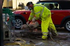 Mann arbeitet mit sah auf der Straße Stockbild