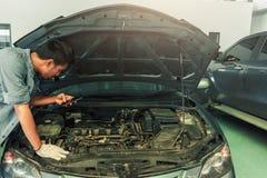 Mann-asiatisches Auto, das Inspektion zu überprüft, um ein Foto für Verlegenheit Reparatur zu machen stockbilder