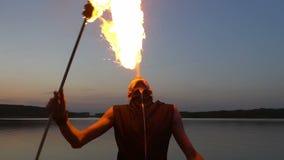Mann atmet Feuer auf einem Hintergrund des Wassers stock video