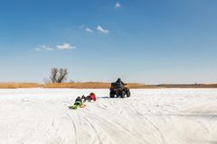 Mann auf ATV-quadbike Reitenschlitten mit Kindern im Schlepptau auf gefrorener Seeoberfläche am Winter Extremer Sport des Winters stockfoto