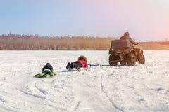 Mann auf ATV-quadbike Reitenschlitten mit Kindern im Schlepptau auf gefrorener Seeoberfläche am Winter Extremer Sport des Winters lizenzfreies stockfoto