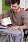 Mann auf bügelndem Hemd des Rollstuhls Stockfoto