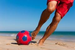 Mann auf balancierender Fußballkugel des Strandes Stockbild