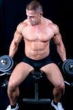 Mann auf Bank mit Gewichten eines Stabes bei der Handausbildung Lizenzfreies Stockfoto