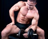 Mann auf Bank mit Gewichten eines Stabes bei der Handausbildung Lizenzfreie Stockfotos