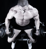 Mann auf Bank mit Gewichten eines Stabes bei der Handausbildung Lizenzfreie Stockfotografie