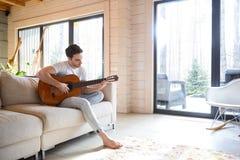 Mann auf Couch mit Gitarre lizenzfreie stockfotografie