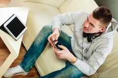 Mann auf Couch mit Kopfhörern Smartphone und Tablette Lizenzfreie Stockfotografie