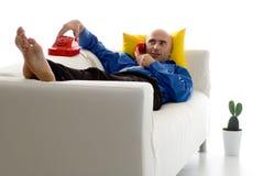 Mann auf Couch mit Telefon Stockfotografie