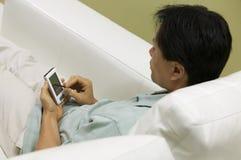 Mann auf Couch unter Verwendung der hohen Winkelsicht PDAs Stockfotos