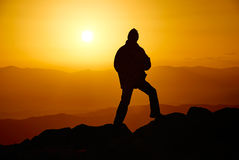 Mann auf dem Berg am Abend stockfotografie