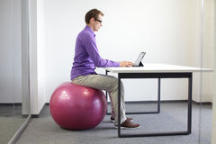Mann auf dem Gymnastikball, der mit Tablette arbeitet Stockfotografie