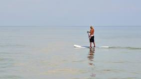 Mann auf dem Radschaufelsegeln entlang dem Strand Lizenzfreie Stockfotos
