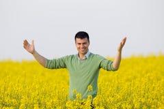 Mann auf dem Rapssamengebiet Stockfotos