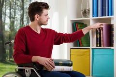 Mann auf dem Rollstuhl, der Bücher setzt Stockfotografie