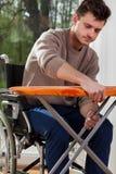 Mann auf dem Rollstuhl, der Eisenbrett vorbereitet Stockfotos